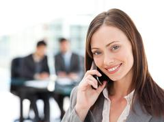 Stock Photo of captivating businesswoman on the phone while her team is working
