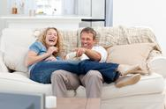 Stock Photo of Lovers watching tv in the living room at home