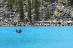 Couple in canoe blue glaciar lake Rocky Mountains Canada - stock photo