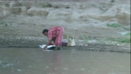 Stock Video Footage of Zoom out from woman washing cloths in river to animals at river banks