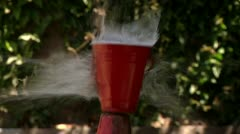 Slow motion shot bullet hit a red cup water outdoors cutaway Intense dramatic Stock Footage