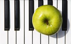 Apple on piano Stock Photos