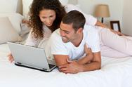 Stock Photo of Lovely couple looking at their laptop