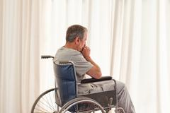 Thoughtful man in his wheelchair - stock photo