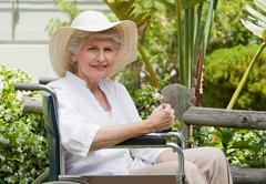 Mature woman in her wheelchair in the garden Stock Photos