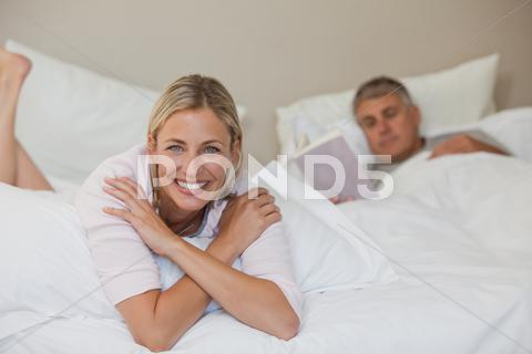 Stock photo of Pretty woman looking at the camera while her husband is sleeping