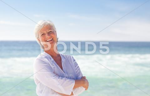 Stock photo of Happy retired woman on the beach