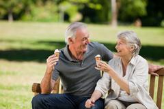 Senior couple eating an ice cream on a bench - stock photo