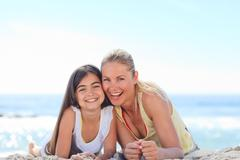 Mother with her daughter on the beach - stock photo