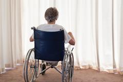 Mature woman in her wheelchair with her back to the camera at home Stock Photos