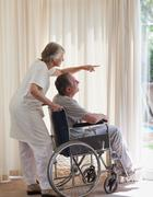 Retired couple looking out the window Stock Photos