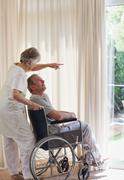 Retired couple looking out the window - stock photo