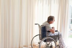 Man in his wheelchair looking out the window Stock Photos