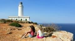 Happy little sisters girls feeling wind in high cliff sea Stock Footage