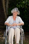 Smiling woman in her wheelchair - stock photo