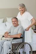 Retired man in his wheelchair with his wife - stock photo