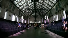 Spectators enter Zuiveringshal West catwalk fashion hall timelapse Stock Footage