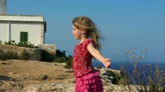 Happy little blond girl feeling wind in high cliff sea Stock Footage