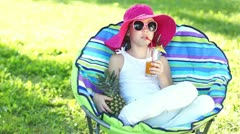 Happy girl drinking fruit juice. Near pineapple and sitting in a chair outdoors Stock Footage