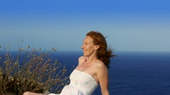 Happy redhead woman feeling wind in high cliff sea Stock Footage
