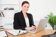 Young beautiful red-haired female in suit typing on her laptop Stock Photos