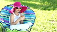 Happy girl drinking juice and sitting in a chair outdoors and looking at came Stock Footage
