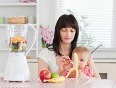 Cute brunette woman pealing a banana while holding her baby on her knees Stock Photos