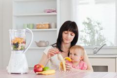 Attractive brunette woman pealing a banana while holding her baby on her knees Stock Photos
