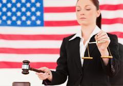 Close up of a young judge knocking a gavel and holding scales of justice - stock photo