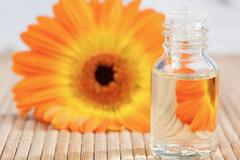 Close up on a glass phial and a sunflower - stock photo