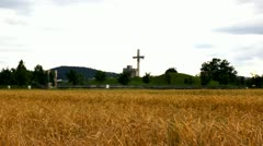 Wheat field with cloudy weather and church cross in background - stock footage