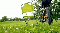 Man sitting on picnic char in green park after bicycling - stock footage