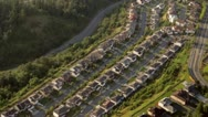 Rows of Suburban Houses On Hillside and Bend in Road - Aerial Stock Footage