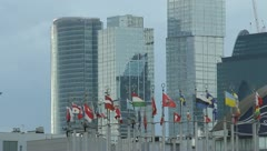 The sky-scrapers behind the flags, strong zoom Stock Footage