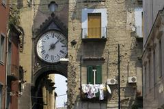 Naples neighborhood clock in ancient buildings Stock Photos