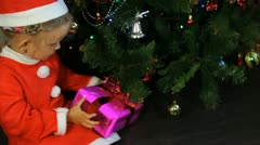 Child Dressed in Santa Claus Putting Gifts Under the Christmas Tree, Winter  Stock Footage