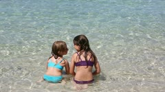 Little girls playing in beach water in ibiza island Stock Footage