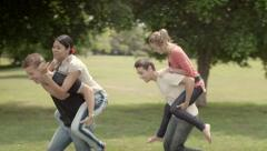Friends having fun, young couples running piggyback in city park Stock Footage