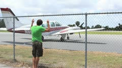 Boy looking at plane through fence Stock Footage