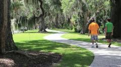 Man and teen boy walking on side walk Stock Footage