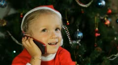 Child Laughing while Talking on the Phone with Santa Claus by the Christmas Tree Stock Footage