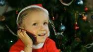 Stock Video Footage of Child Laughing while Talking on the Phone with Santa Claus by the Christmas Tree