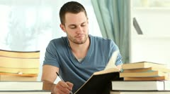 Writer taking notes while reading books Stock Footage