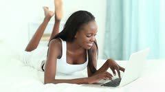 Smiling woman typing on a white laptop Stock Footage