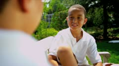 Little Ethnic Boys Sitting Garden Bench Stock Footage