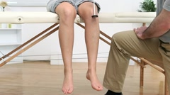 Physiotherapist testing the reflex of a woman - stock footage