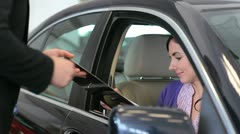 Woman in her car signing a document - stock footage