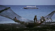 Woman lying in a hammock and reading a book Stock Footage