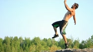 Stock Video Footage of Young man does running backflip off of a cliff.
