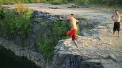 Young man does a flip off of a cliff. - stock footage
